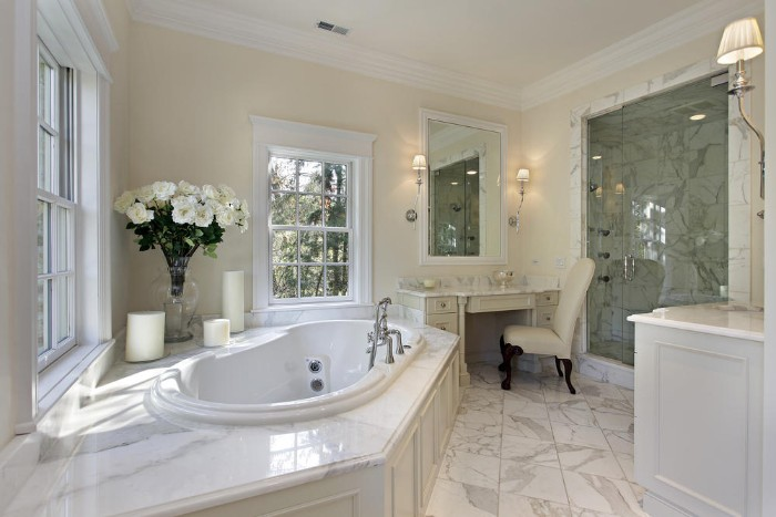 classic bathroom with marble floor, vintage white furniture, antique vanity with an off-white chair, round elevated bathtub, and a bouquet of white flowers