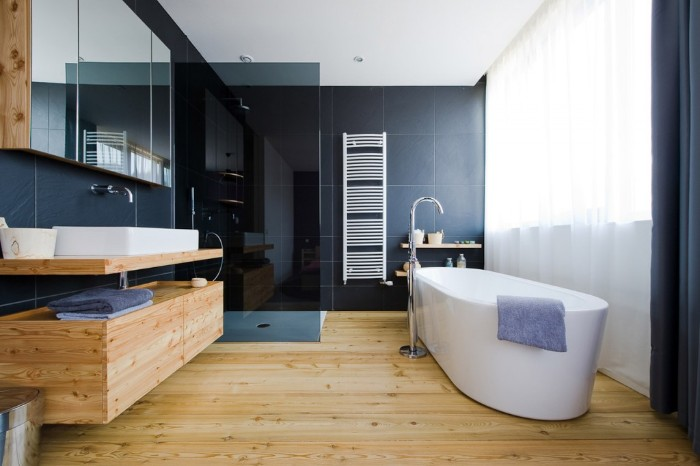 curtains in white, decorating a large window, inside a room, with pale beige wooden floor and cupboards, master bath remodel, oval white bathtub, navy blue walls