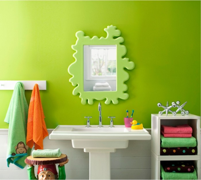 decorative mirror in a splatter-like, pale green frame, mounted on a lime green wall, bathroom paint colors, white sink and cupboard, and colorful decorative items