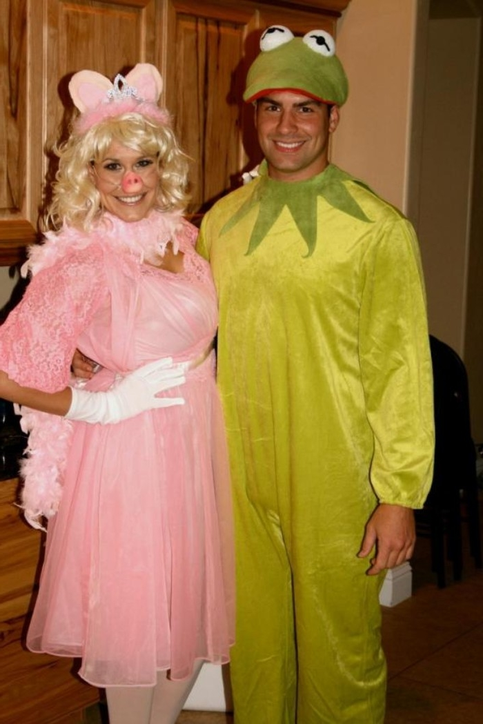 kermit the frog, and miss piggy, costumes inspired by the muppet show, woman dressed in pink, with a curly blonde wig, and a pig mask, man in a frog onesie