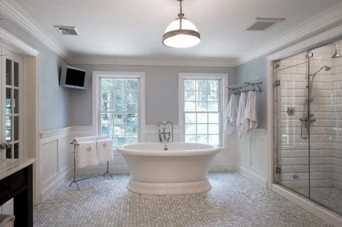 light grey walls, in a room with white paneling, and mosaic tiles on the floor, glass shower cabin, and a white, vintage style tub