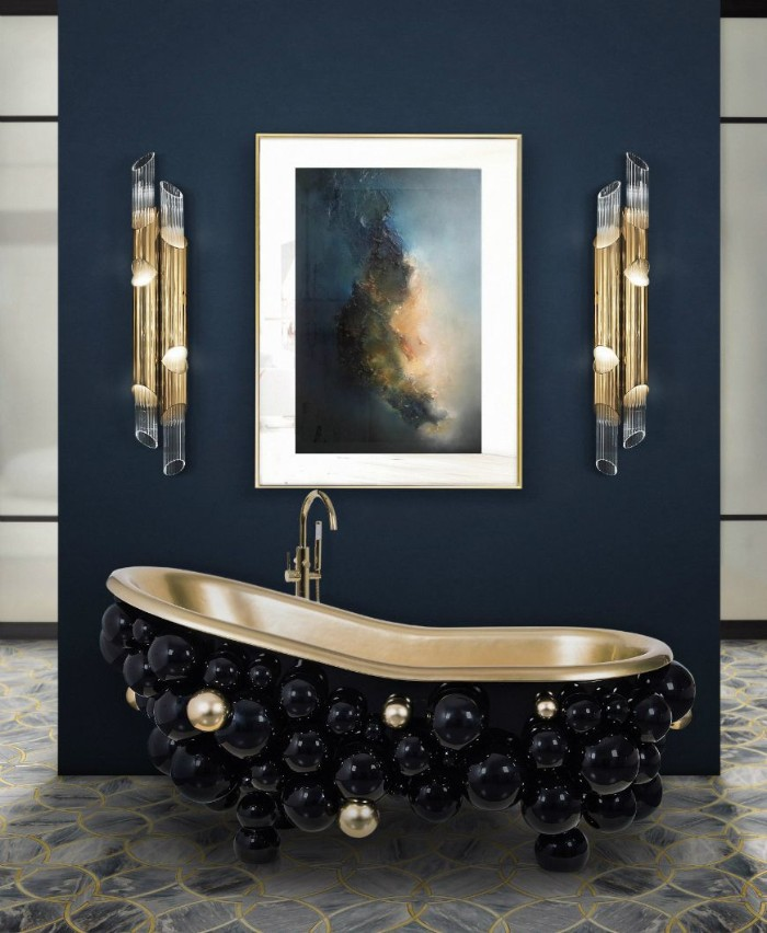 decorative spheres in black and gold, decorating a vintage-style bathtub, near a navy blue wall, decorated with a painting, and two modern lamps, bathroom picture ideas, stone tiled floor