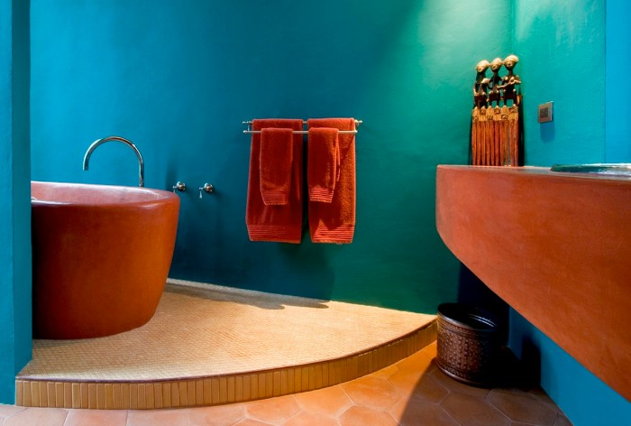terracotta bathtub and sink, in a room with a beige stone tiled floor, and ocean blue walls, two sets of orange towels