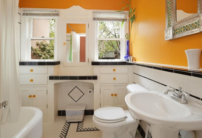 white bathroom furniture, in a room with orange walls, best paint for bathrooms, two windows and a mirror, bathtub a toilet and a sink