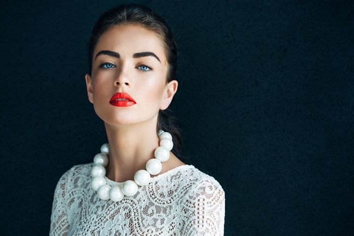 holiday makeup 2017, young blue-eyed woman, dressed in a white lace top, with an oversized pearl necklace, and bright red lipstick