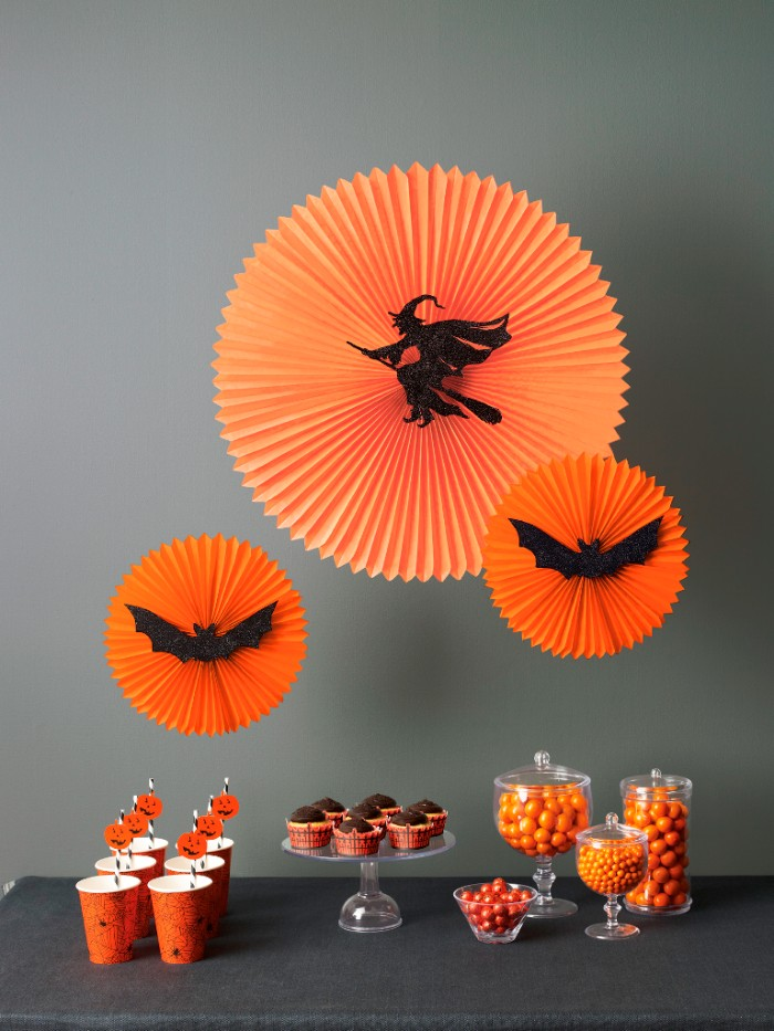 halloween party decoration ideas, three round orange paper ornaments, decorated with black cutouts, shaped like a witch flying on a broomstick, and two bats, hanging over a table, with snacks and drinks