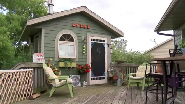 deck made of wood, with a small pastel green shed, featuring a door and a wndow, garden shed ideas, two light green garden chairs nearby