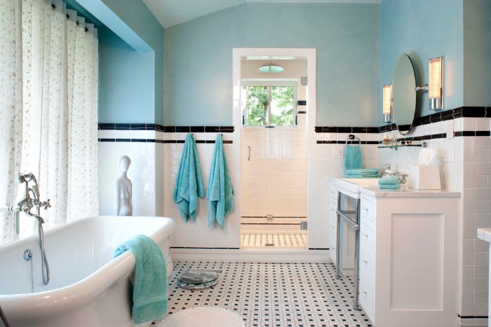 white shower curtains, with a pale pattern, near a vintage style white bathtub, in a room with pale blue walls, half-covered with white subway tiles, featuring black details