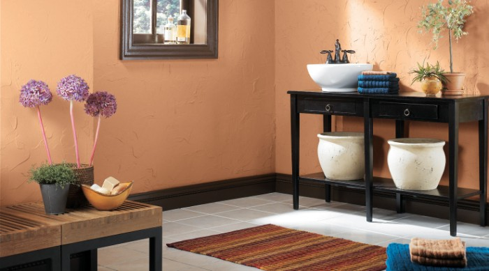textured walls in peach pink, inside a bathroom, with black and brown furniture, a small window, and several indoor plants