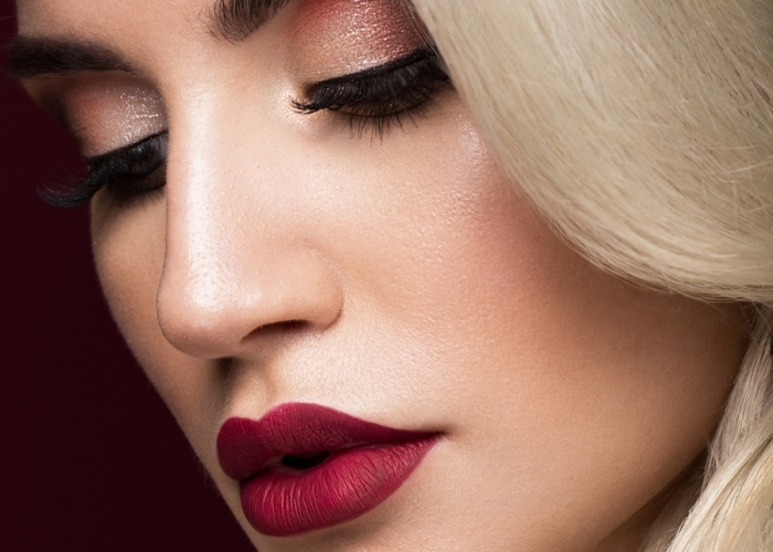 burgundy red lipstick, shimmering pale brown eye shadow, and long fake lashes, christmas makeup ideas, worn by a platinum blonde woman