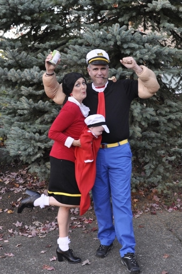 olive oyl and popeye the sailor, duo halloween costumes, man dressed like a captain, with a pipe and a can of spinach, woman in red jumper, and black skirt, holding a baby