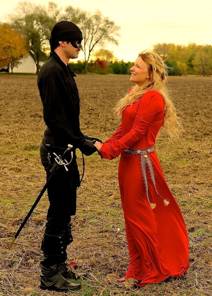 buttercup and wesley, costumes inspired by the film the princess bride, man dressed in black, with a mask on his face, holding the hands, of a woman with long curly blonde hair, wearing a red gown