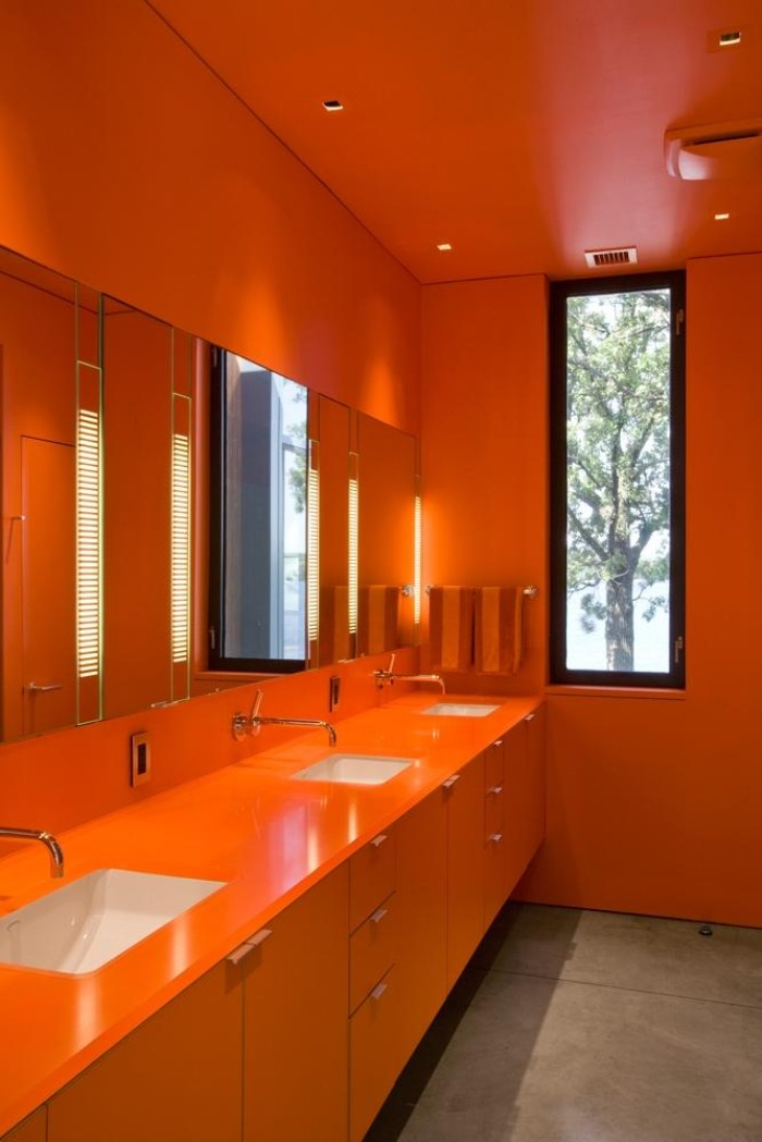 brick orange-colored walls and cupboards, with small white sinks, best paint for bathrooms, in a large room, with a tall narrow window, and several mirrors