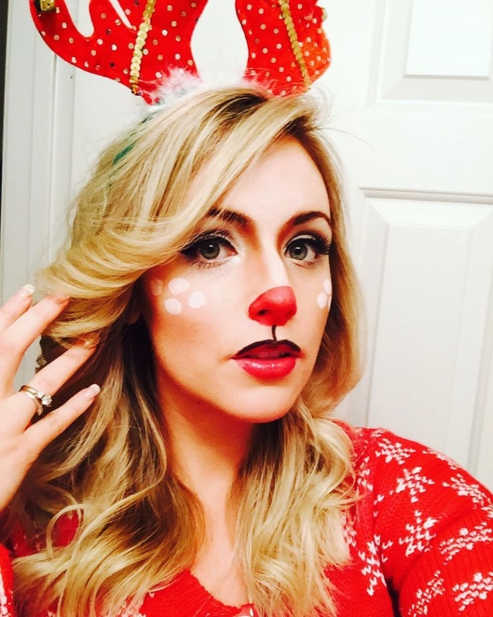 festive makeup for chistmas, reindeer face paint, with a red nose, worn by a blonde woman, wearing a red christmas sweater, and a head decoration with antlers