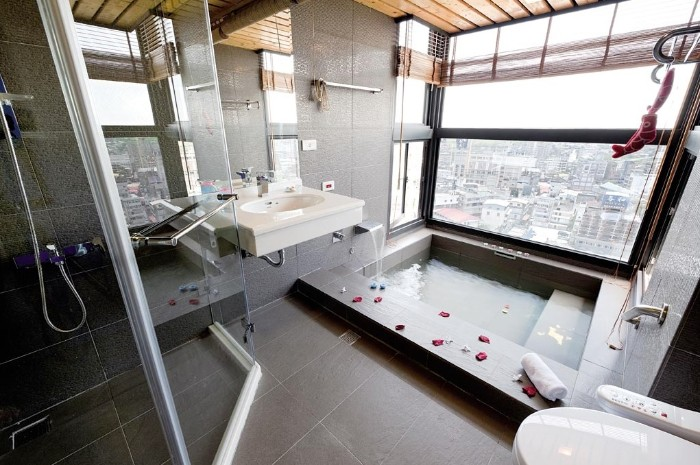 tub with rectangular shape, filled with water, and decorated with scattered rose petals, spa like bathrooms, large window overlooking a city