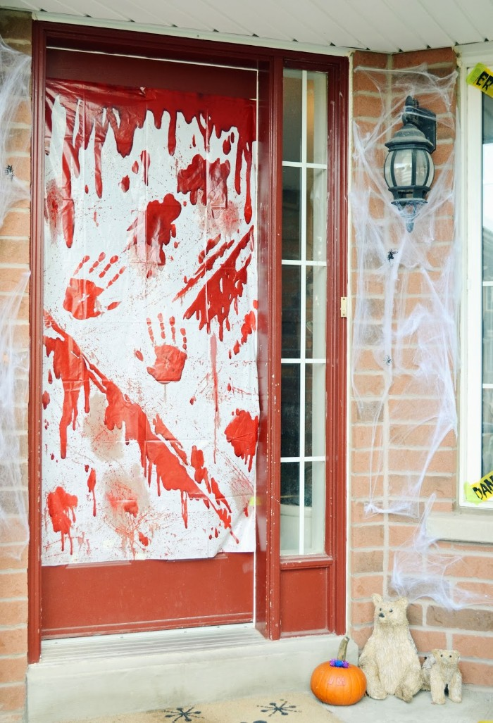 bloody arm prints and splatters, painted on a sheet of white plastic, stuck to a door, scary outdoor halloween decorations, fake cobwebs and a pumpkin nearby