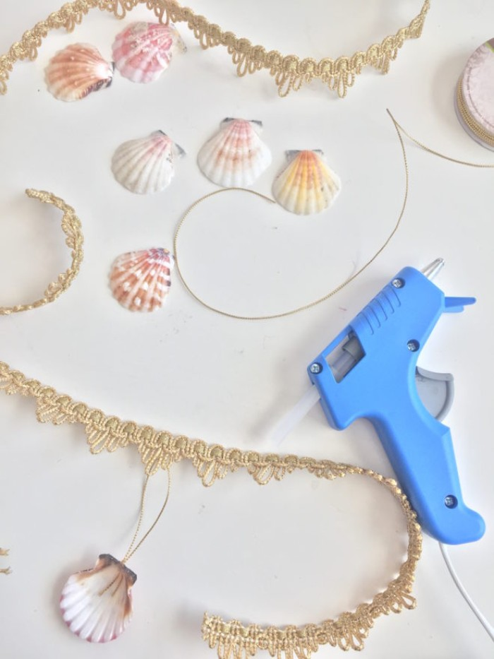 seashells in white, pink and pale orange, on a white surface, near some gold-colored crochet lace, some string and a glue gun, couple costume ideas, mermaid and merman diy