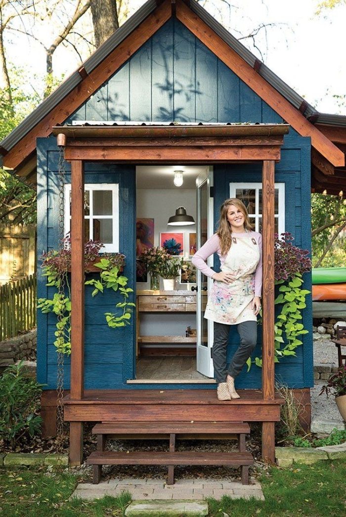 smiling blonde woman, with hand on her hip, standing in front of a blue wooden shed, its door is open, revealing an artist studio inside, she shed interiors, framed artworks and flowers