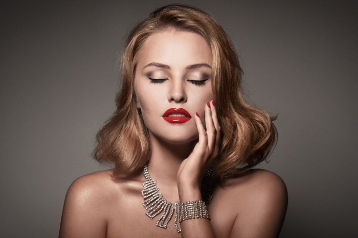 diamond necklace and matching bracelet, worn by a young pale woman, with wavy dark blonde, shoulder length hair, christmas eyeshadow with smokey effect, glossy red lipstick