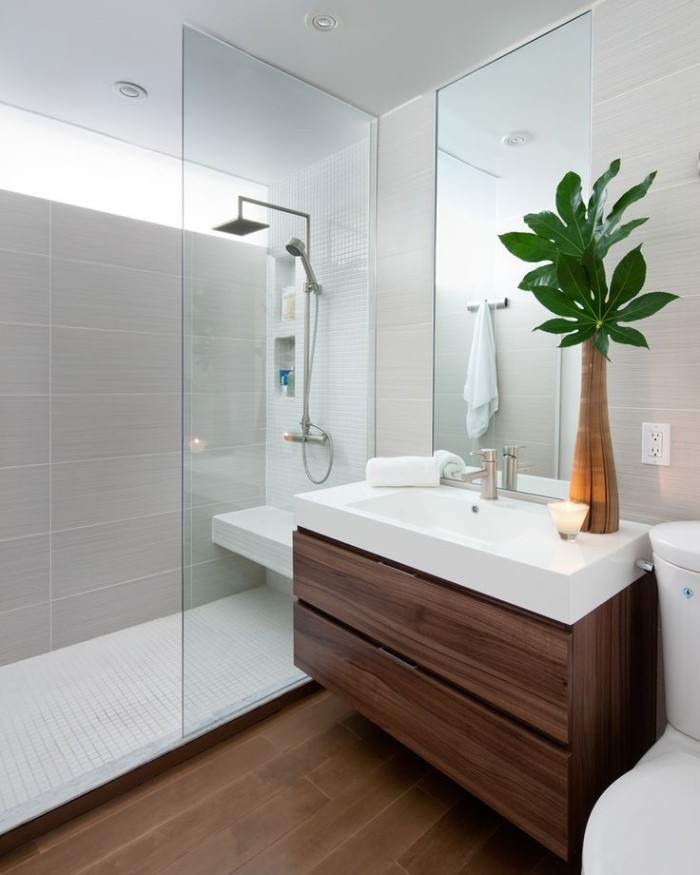 toilet seat in white, near a rectangular white sink, placed over a dark brown cupboard, master bathroom remodel, shower cabin with a glass divider