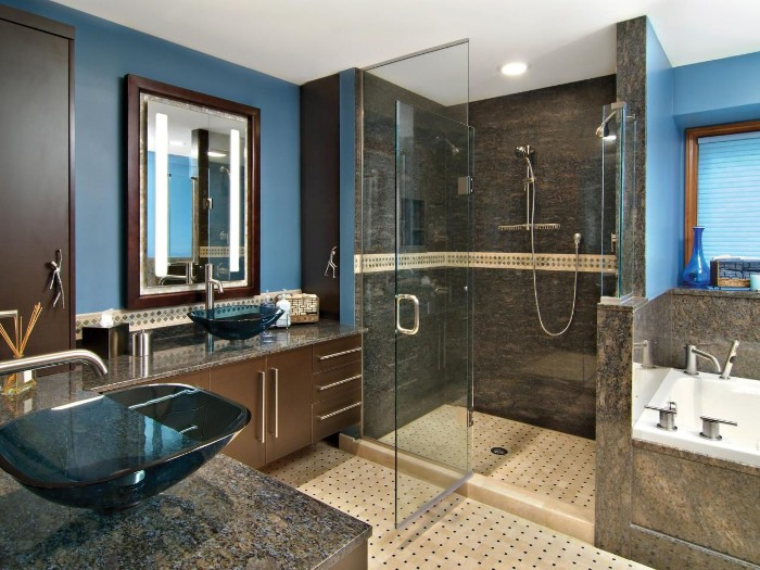open door of a glass shower cabin, inside a bathroom, with blue and grey walls, beige tiled floor, and brown cupboards