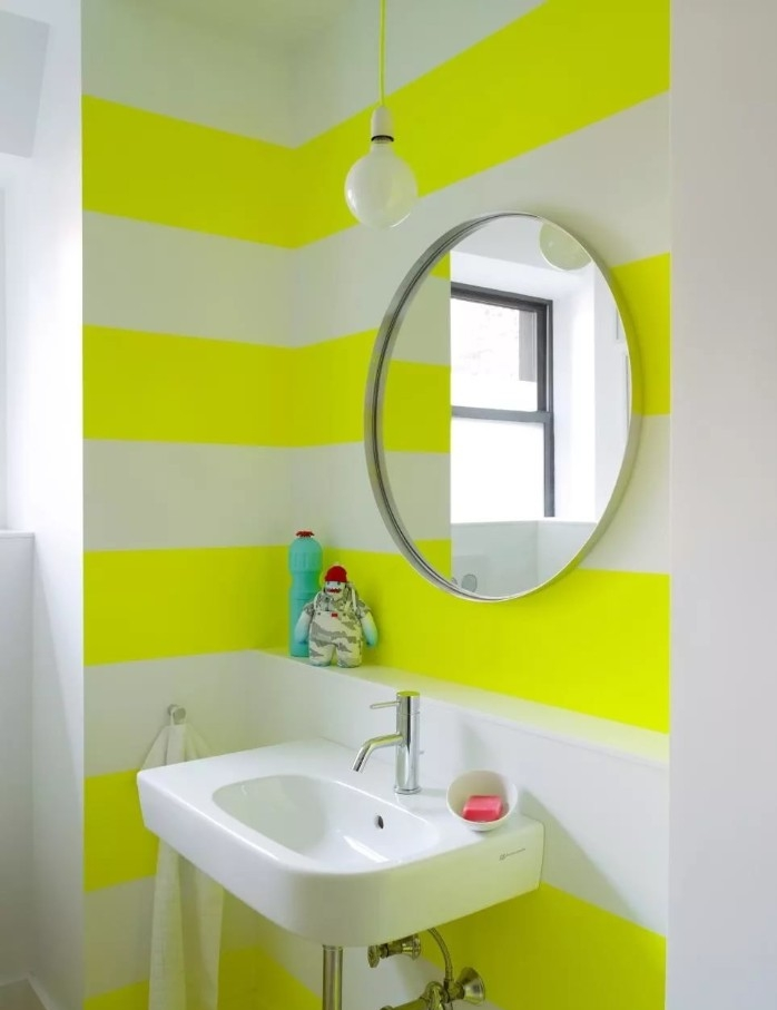best paint for bathrooms, white and yellow stripes, on a bathroom wall, decorated with a round mirror