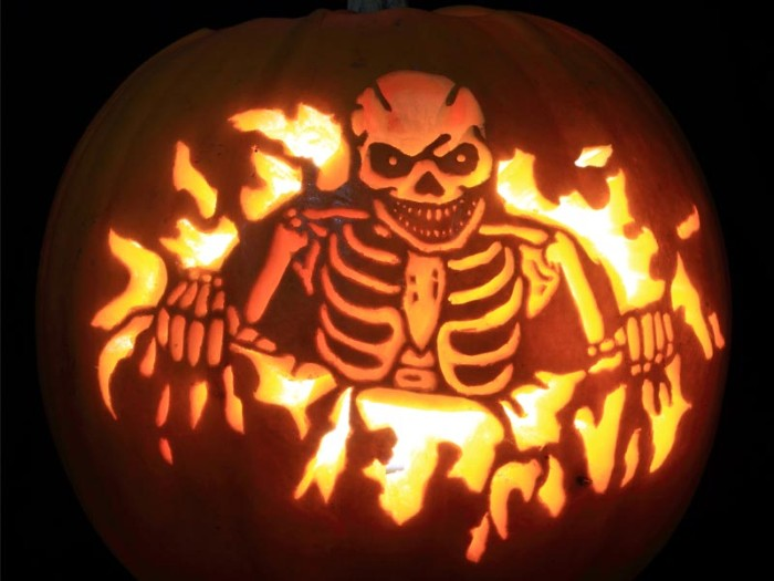 evil laughing skeletton, carved on an orange pumpkin, lit with candles from within, skeleton pumpkin, in a dark space