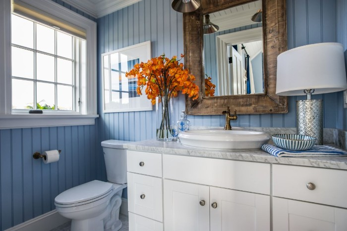 ornamental wooden frame, around a rectangular mirror, mounted on a pale blue wall, with a striped pattern, small bathroom paint colors, white cupboard with a marble countertop, toilet and a window