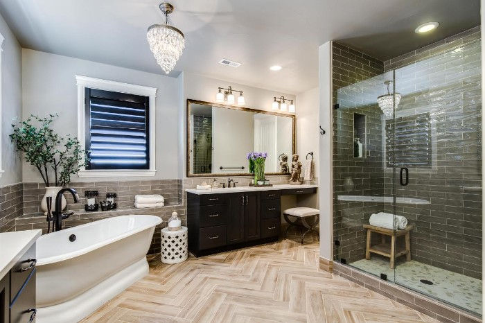 laminate floor in pale beige, inside a bathroom, with dark grey subway tiles, a glass shower cabin, and a vintage-style white bathtub
