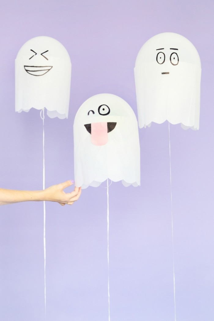 balloons in white, decorated with paper, to look like ghosts, with funny hand-painted faces, halloween party decoration ideas, hand holding one of the balloons