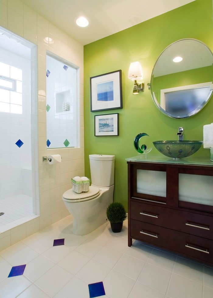 bathroom accent wall in lime green, inside a room covered in white tiles, with blue details, dark brown cupboard with a sink, toilet and two framed images