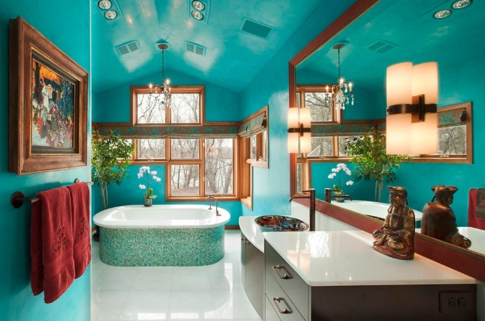 mosaic tiles in different shades of blue, covering the outside of a bathtub, in a spacious room, with turquoise walls and ceiling, best bathroom paint colors, window and a large mirror