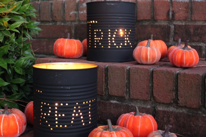 cans painted in black, wit holes spelling the words trick and treat, containing lit candles, haunted house decorations, placed on a brick staircase, with several orange pumpkin ornaments nearby