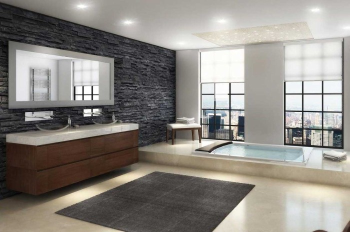coarse natural stone tiles in pewter grey, decorating the wall of a bright room, with two large windows, bath remodel ideas, inbuilt rectangular tub, smooth pale beige floor