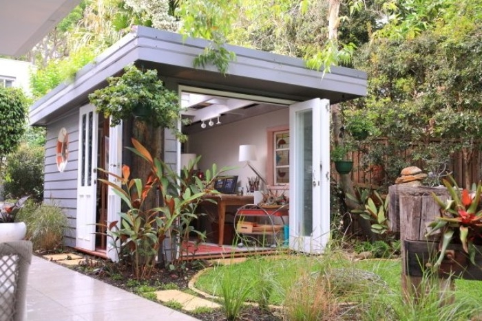 bushes and plants, growing on and around a small, pale grey shed, with white doors, and skylight windows, she shed ideas, for your garden