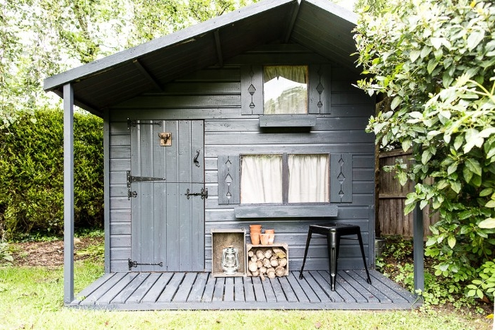 hut in the forest, made of dark grey wood, with two windows and one door, rustic she shed idea