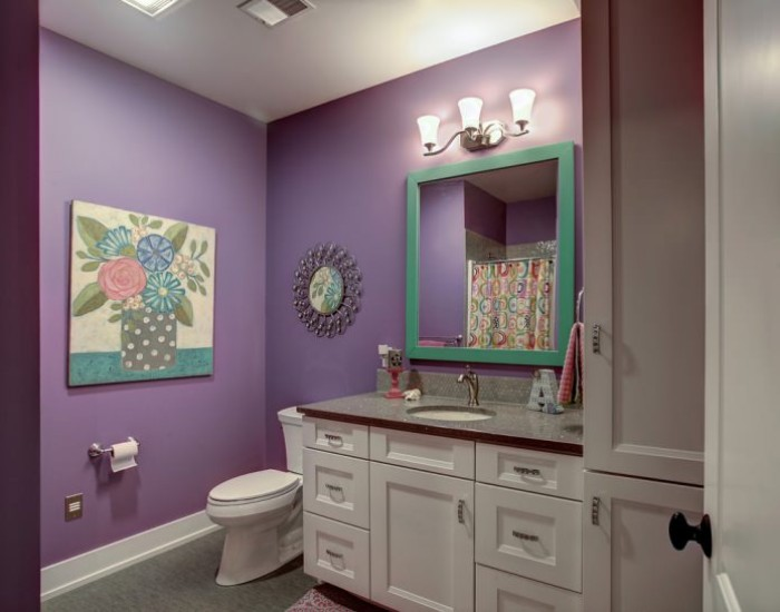 painting of a flower vase, decorating the violet walls of a room, with white furniture, a toilet and a large, square mirror in a turquoise frame, small bathroom paint colors