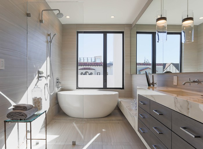 long rectangular mirror, decorating the wall of a btahroom, with a white oval bathtub, a shower area, and dark brown cupboards, with marble counter tops