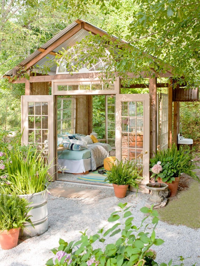 bright orangery style shed, made of wood and glass, she shed ideas, doors opened to reveal a sofa, with lots of cushions inside