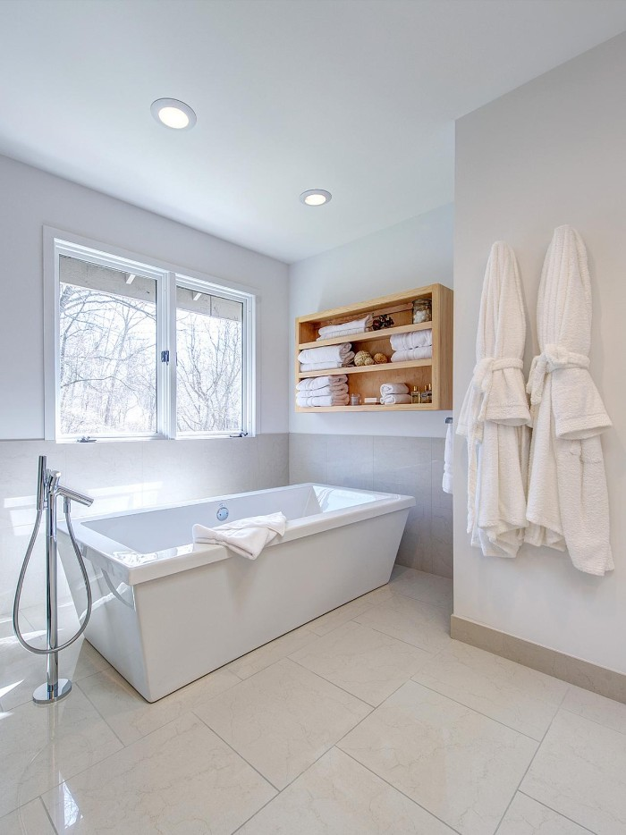 rectangular bathtub in white, inside a bright room, with a window, and pale beige floor, master bath remodel, two white bathrobes