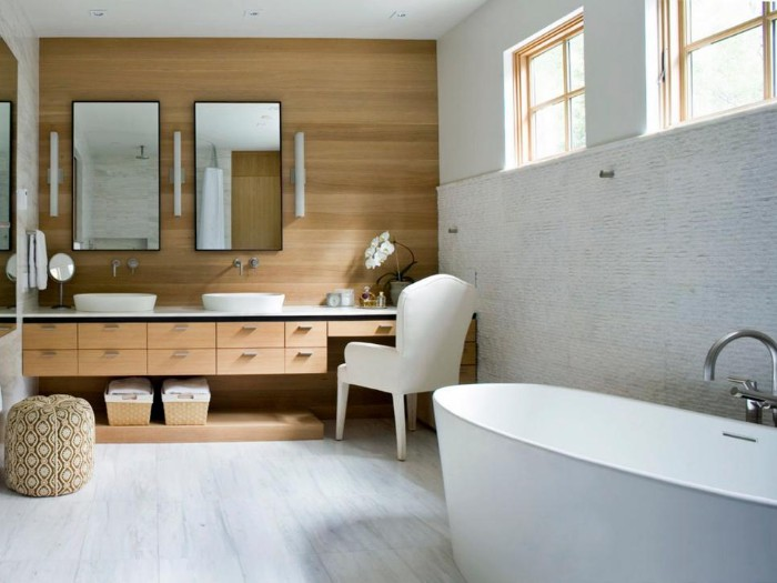 a set of two mirrors, mounted on a wall, covered with wooden panels, oval bathtub in white, cupboards and two swquare windows
