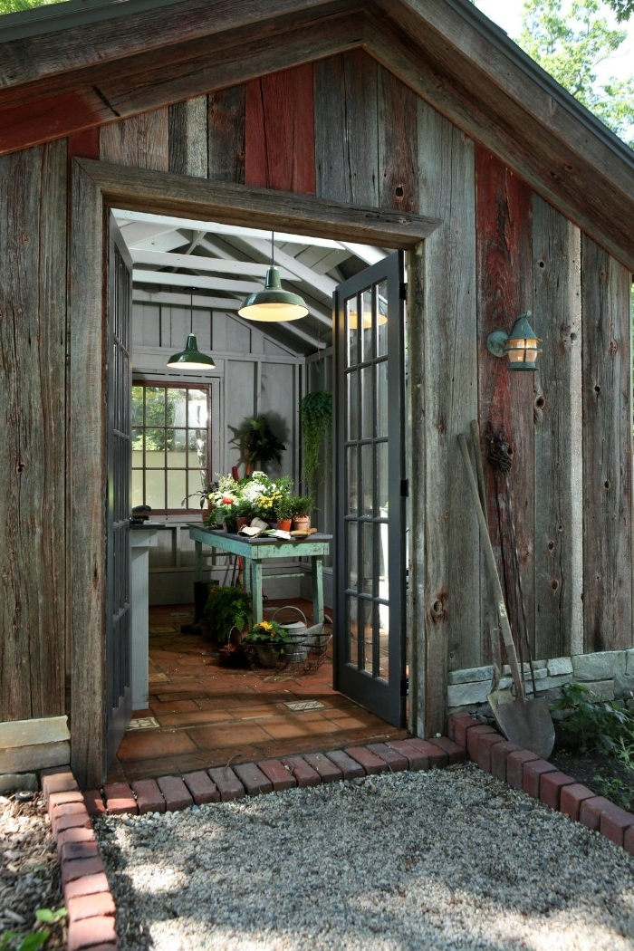 grey and brown wooden shed, with open double doors, revealing a vintage, duck's egg blue table, with flowers and potted plants, she shed