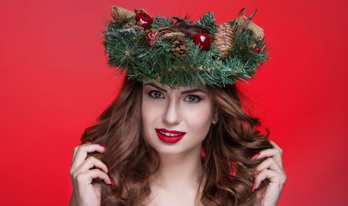 pine branches wreath, decorated with pinecones, and christmas ornaments, on the head of a brunette woman, with holiday makeup and wavy hair
