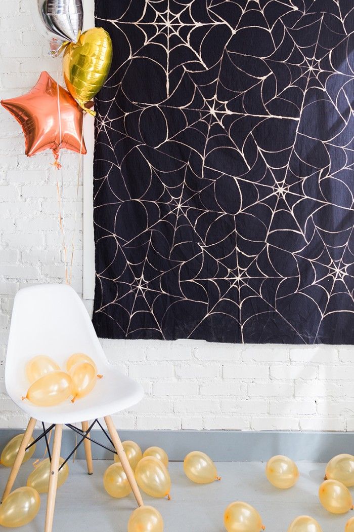 rectangular piece of black fabric, decorated with a pale cobweb pattern, hanging on a white brick wall, halloween decorations, pale yellow ballons, and a white chair, larger balloons shaped like stars and a heart