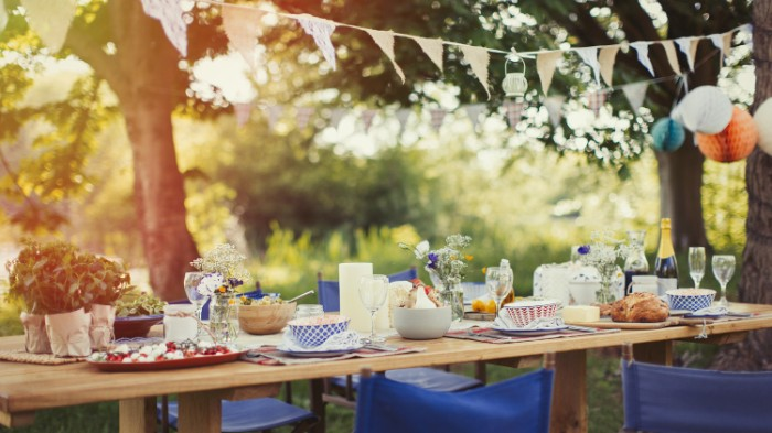 garden party 50th birthday ideas, table in a garden, set for a festive meal, several blue folding chairs, garlands and colorful paper decorations