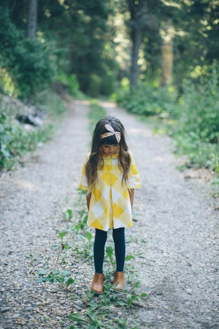 small girl dressed in a white and yellow, checkered tunic dress, over black leggings, toddler thanksgiving outfit, headband and brown ankle boots