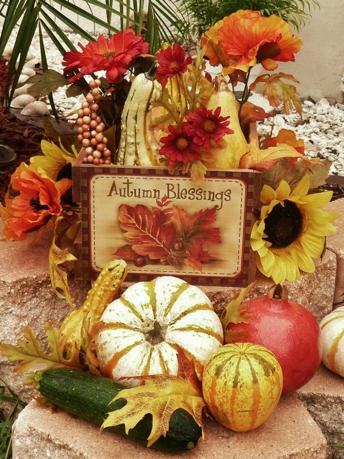 courgette and pomegranate, gourds and pumpkins, and faux flowers in red and orange, near a small wooden sign, decorated with fall leaves, and featuring the message autumn blessings