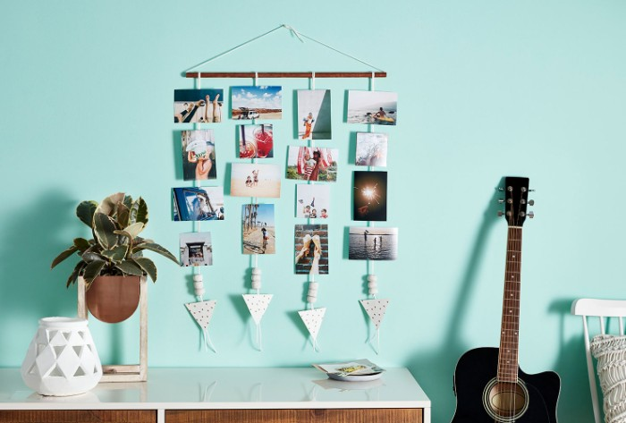 photos hanging on strings, attached to a small wooden pole, hung on a pale blue wall, near a potted plant, and a guitar, teenage girl room ideas