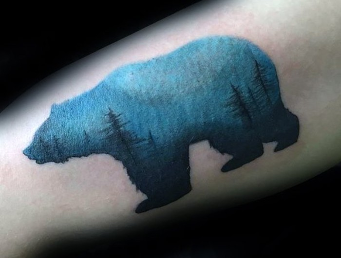 nature-inspired small tattoos with meaning, a bear-shaped watercolor-effect tattoo, decorated with multiple fir trees, in dark blue, on a light blue background
