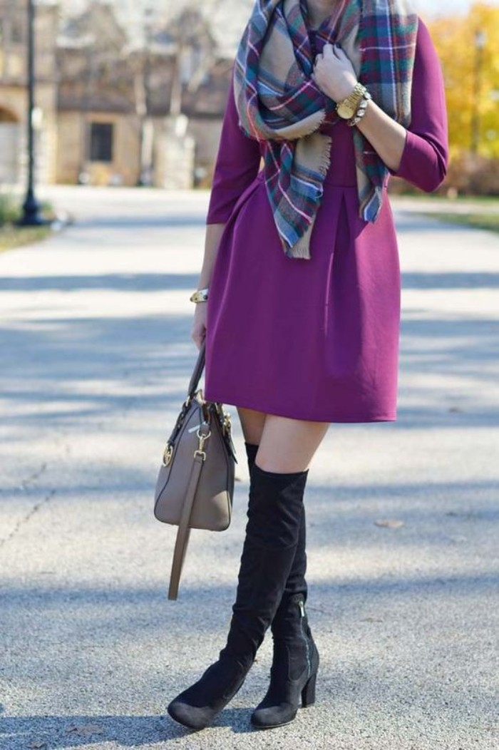 purple mini dress, worn with a plaid blanket scarf, and over-the-knee black suede boots, by a slim woman, holding a beige bag